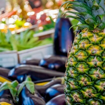 at the fruit market with a pineapple aubergine background