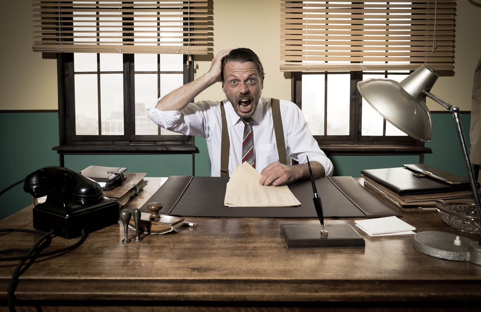Businessman with mouth open working at desk and checking paperwork.
