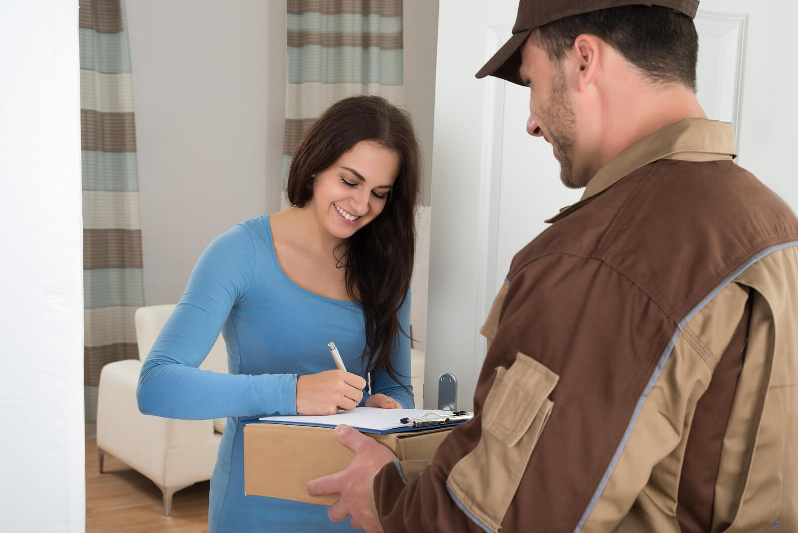 Young Woman Signing While Receiving Courier From Delivery Man