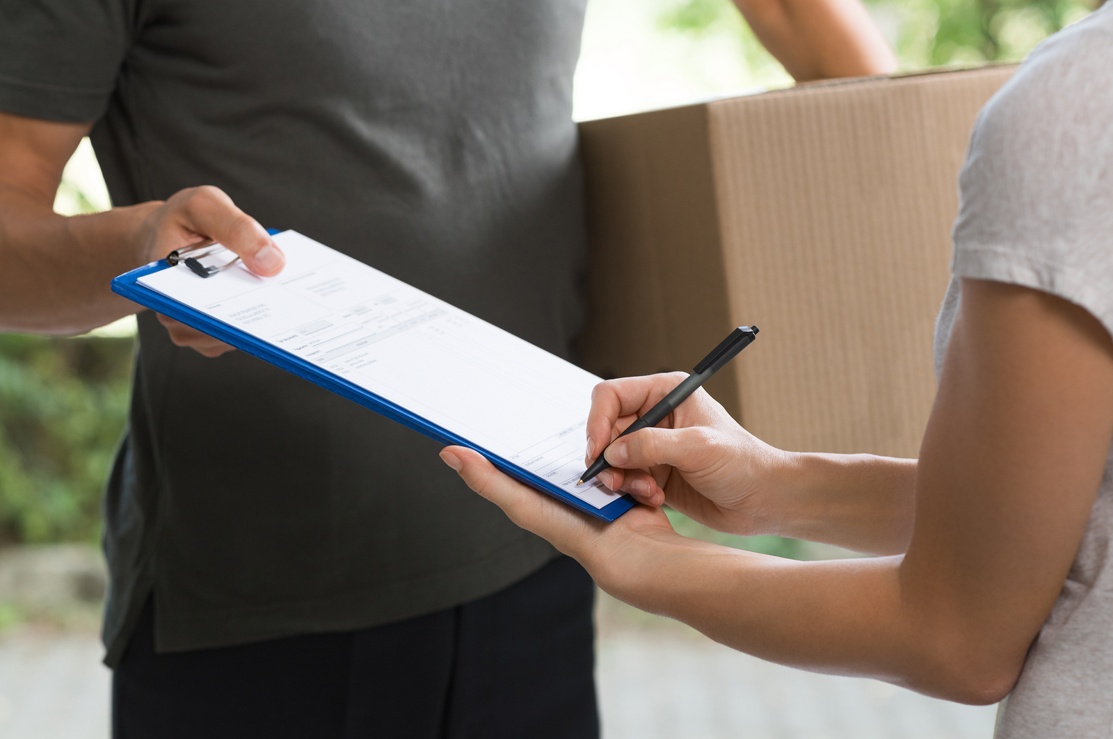 Woman signing receipt of delivery package. Courier man carrying